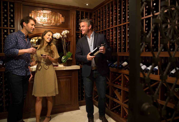 two men and a woman in the wine room selecting a bottle