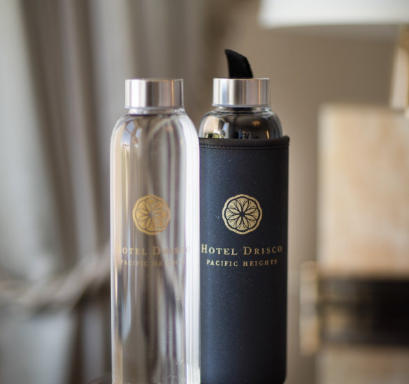 complimentary glass water bottles in a guestroom