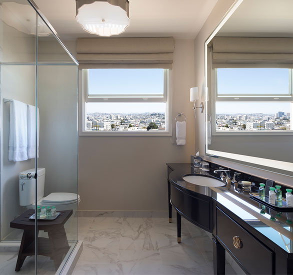 bathroom with a glass enclosed shower and view of the city
