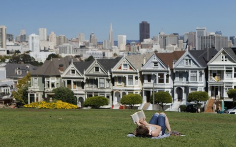 girl reading a book on the lawn with victorian homes in the back