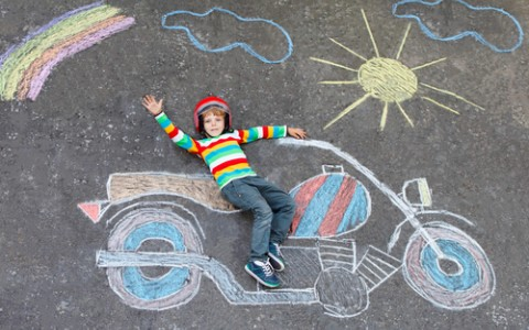 little boy laying on sidewalk chalk art of a motorcycle