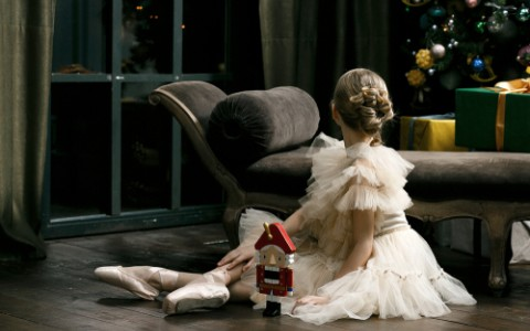 young ballerina in tutu with nutcracker toy