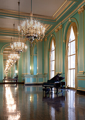Large ballroom with mint green walls, gold accents, chandeliers & grand piano