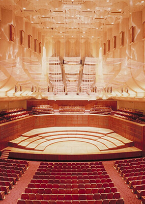Large auditorium with orchestra set stage & red chairs for audience