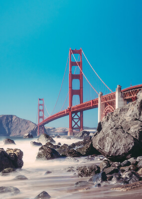 Red Golden Gate Bridge surrounded by rocks & fog