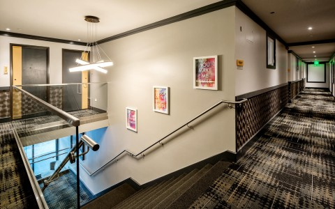 A photo of the hotel hallway and stairwell, water color inspirational quotes are on the wall