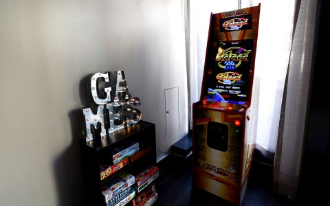 A bookshelf with board games on the right, with light up letters spelling GAMES on top, an old school arcade game on the right.