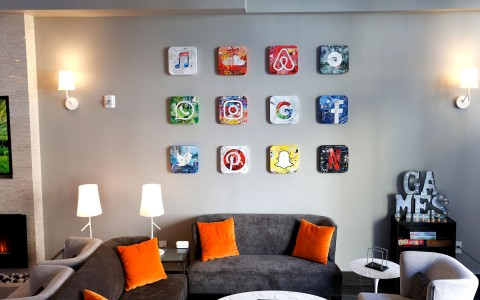 Photo of wall art in the lobby. The art is water color tiles representing different mobile apps, like iTunes, Soundcloud, AirBnB, Uber, Phone, Instagram, Google, Facebook, Twitter, Pinterest, Snapchat and Netflix.  There is also a grey couch with orange p