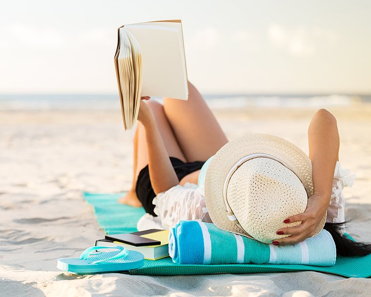 A woman laying on a towel at the beach reading a book