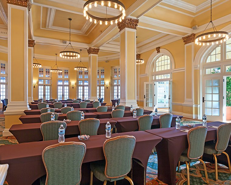 Angled view of rows of tables in a room with tall ceilings and lots of windows