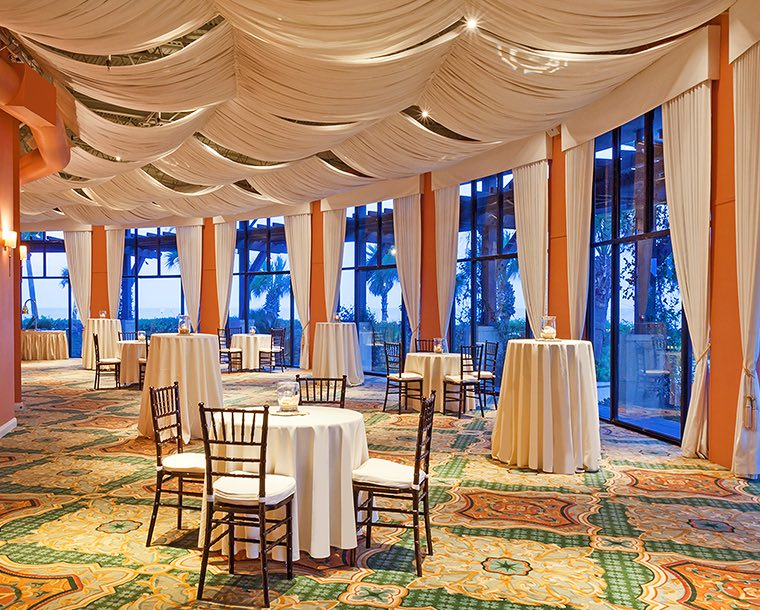 A mixture of cocktail tables and seating tables in an event room with an wall full of windows. White curtains are draped across the ceiling and gather in between each window.