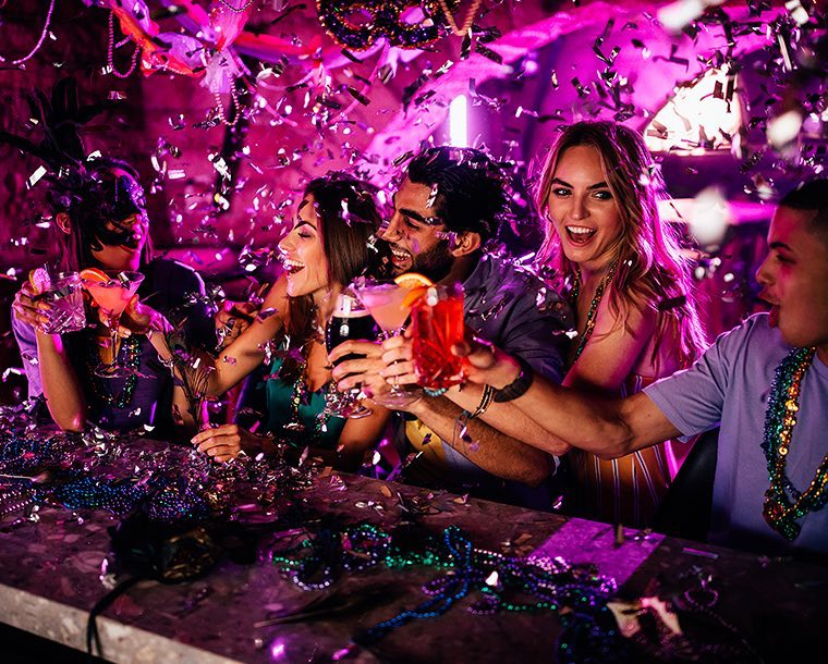 A group of friends toasting at the bar with confetti flying around and pink lights in the background