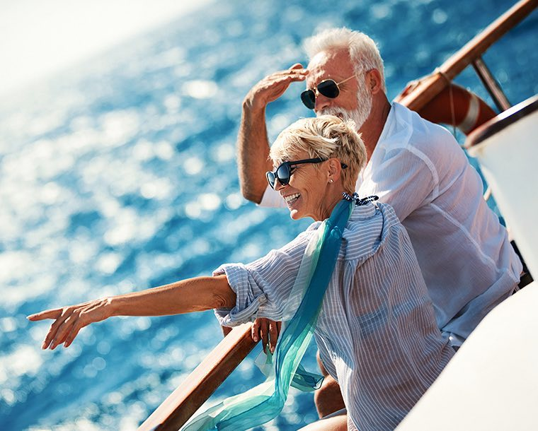 An elderly couple on a boat in the water pointing to something in the distance
