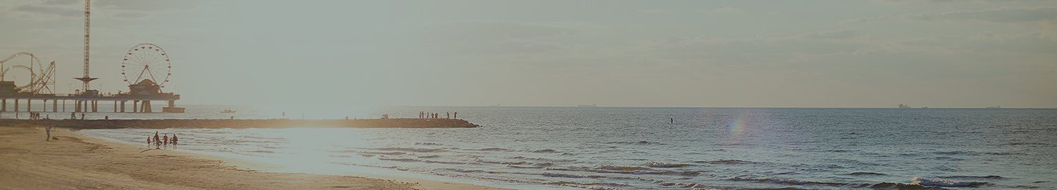 wide view of water from beach with the sun and a pier carnival in the background