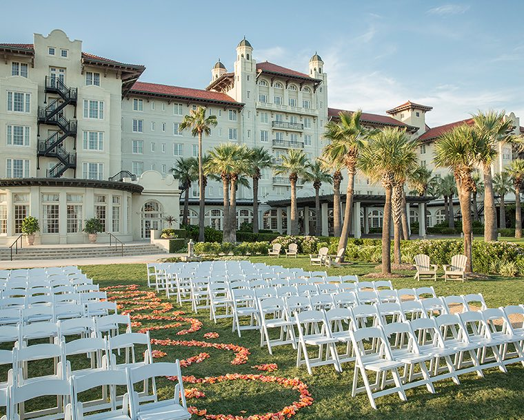 A wedding ceremony set up on the lawn outside Hotel Galvez with rows of white folding chairs and decorative flowers down the isle