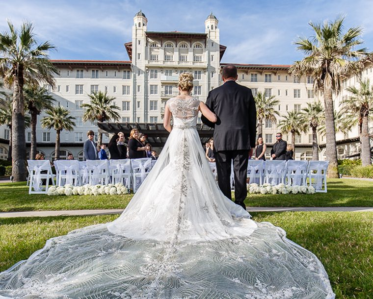 Behind view of a man walking his daughter down the isle at her wedding on the lawn outside Hotel Galvez