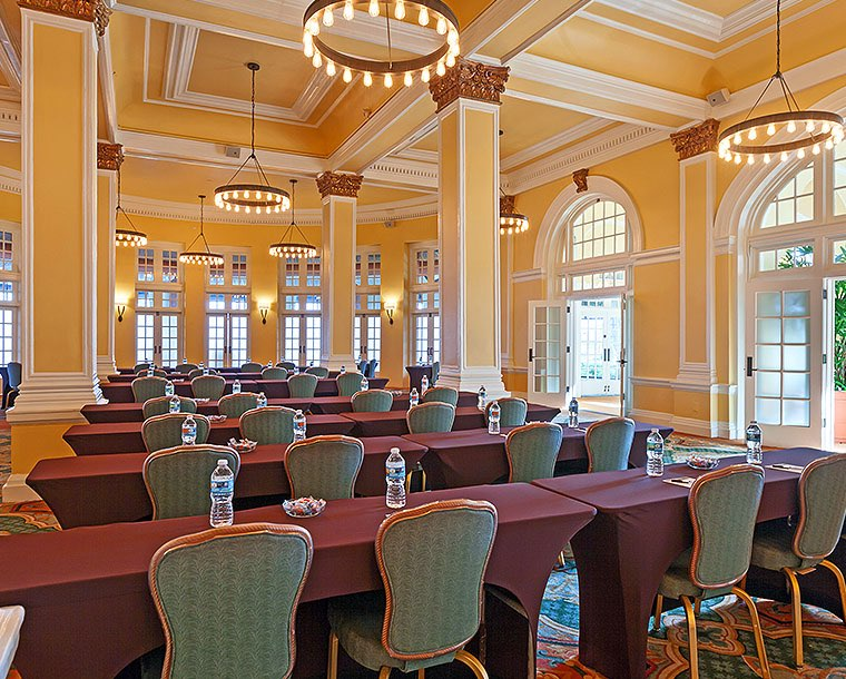 An large event space with yellow walls and white crown molding and rows of long tables draped in maroon tablecloths and blue cushioned chairs