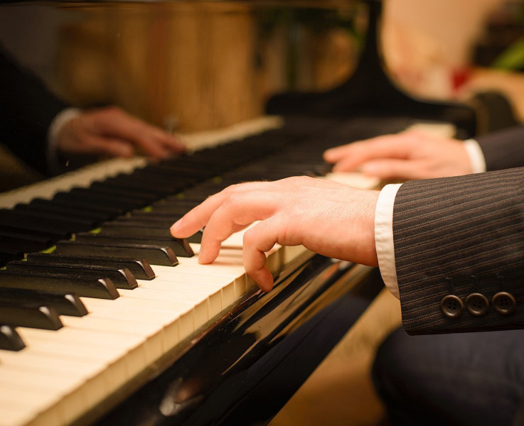 A man's hands playing the piano