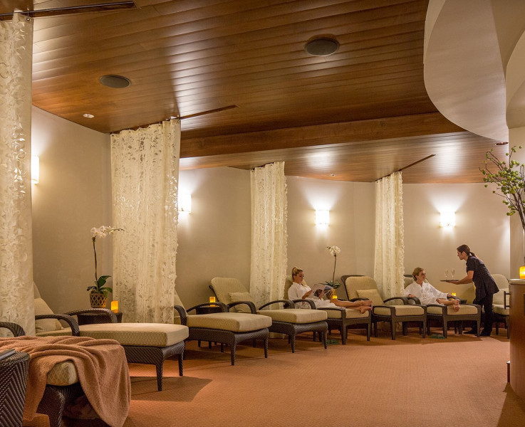 The spa area with cushioned lounge chairs divided individually by white curtains