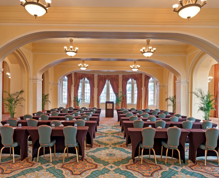 A room set up for an auditorium style meeting with rows of tables and chairs and a podium at the front