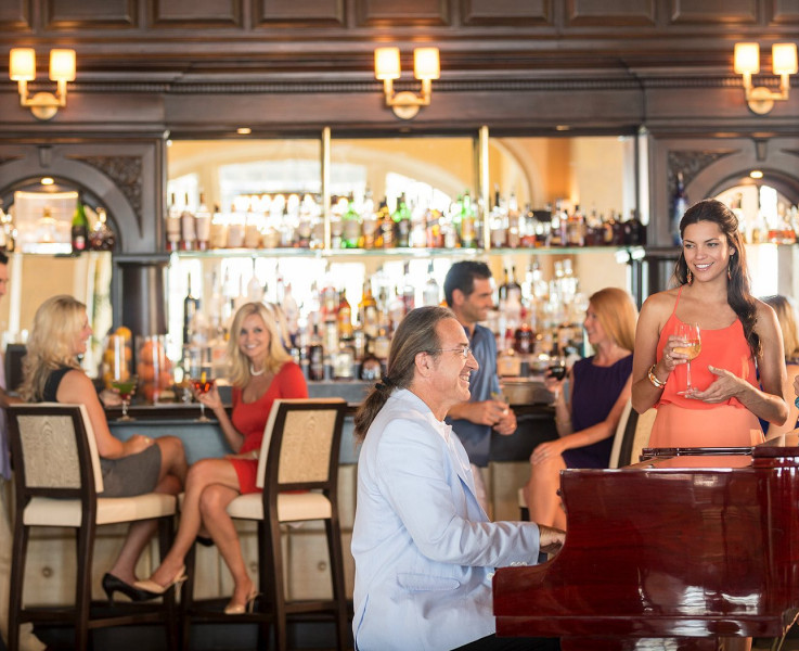 A man playing the piano at the bar area with people standing around the piano listening and sitting at the bar