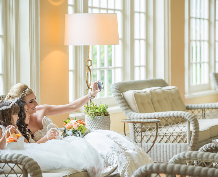 A bride sitting on a wicker couch taking a selfie with the flower girl