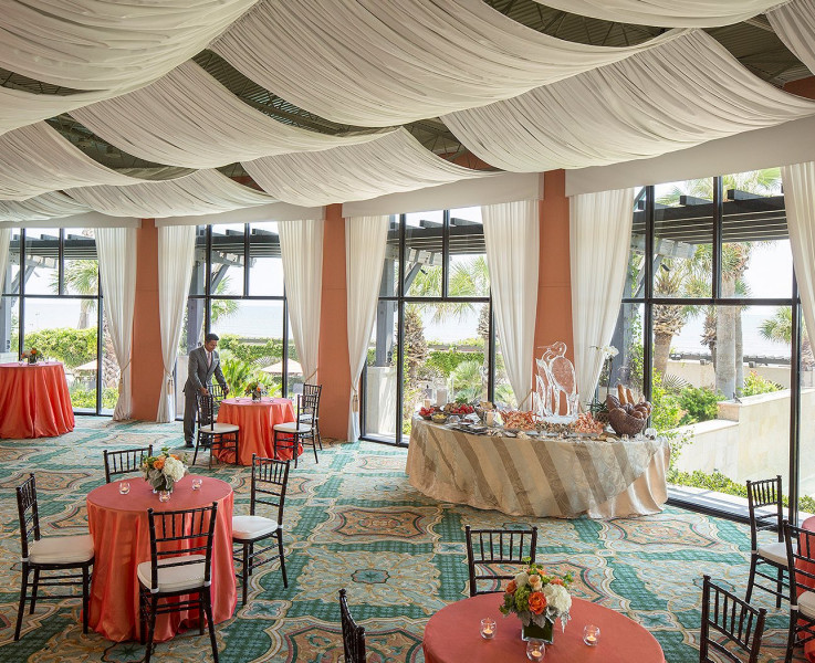 A colorful event space with cocktail tables, seating tables, and a buffet table. The ceiling is draped with white curtains that gather at the windows on the wall