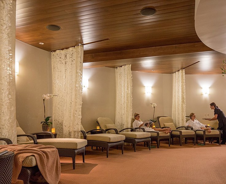 spa interior with chaise lounges and guests being served drinks by staff