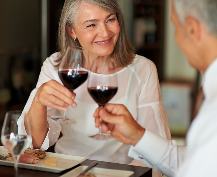 senior couple toasting glasses of red wine at a table