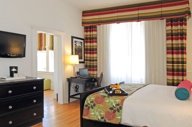 king bed in a room with a desk and colorful curtains