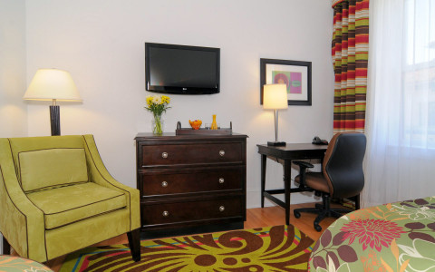 hotel room with desk and green chair next to dresser