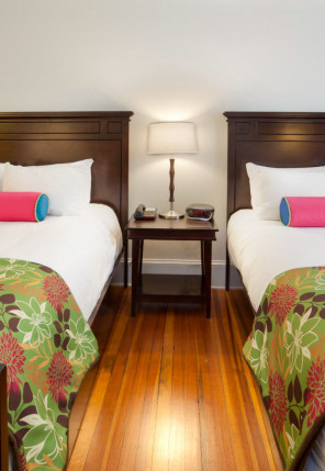 Two queen beds in hotel room with two pink pillows