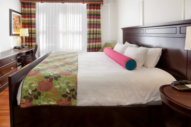 room with king bed and green blanket