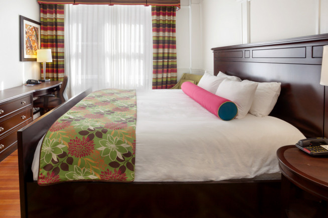 queen bed with colorful blanket and pink pillows