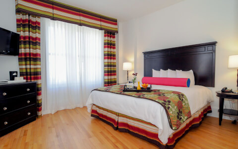 King bed with wood bed frame and colorful curtains