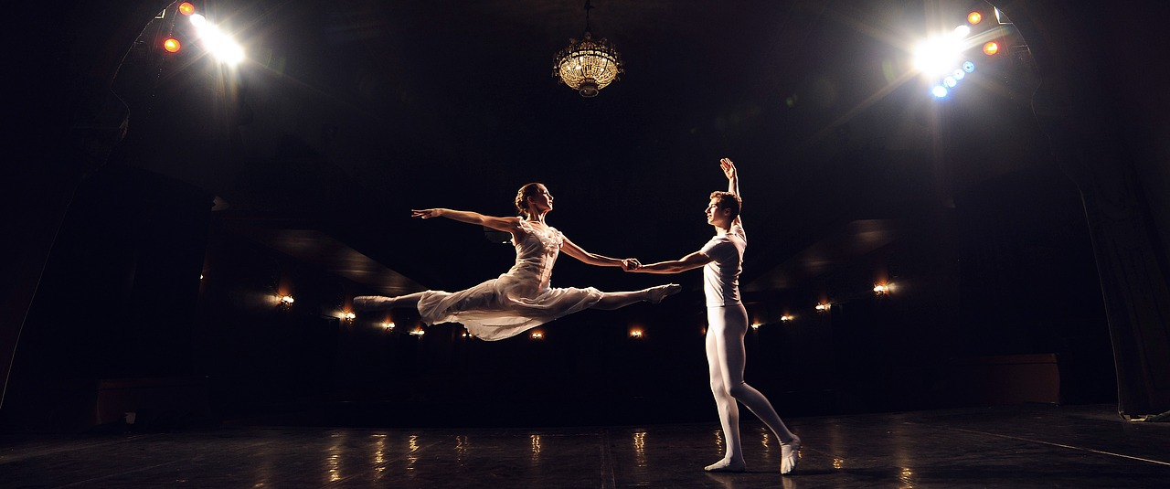 Male and female ballet dancer in white on stage
