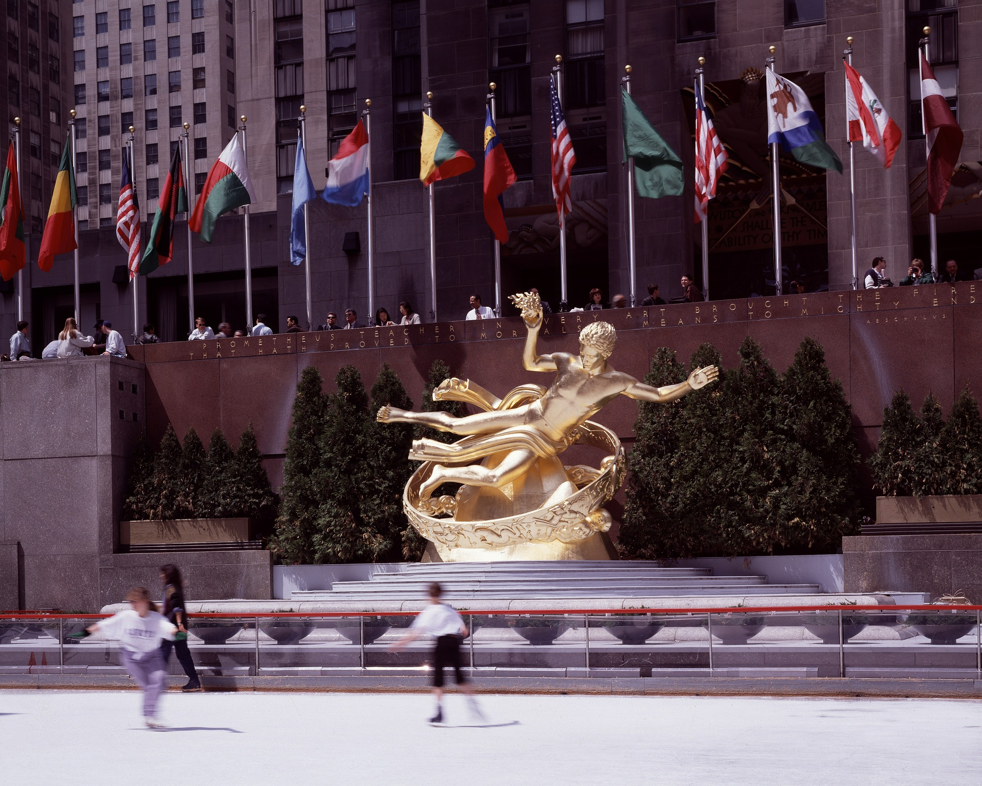 Two ice skaters at Rockefeller Center in front of gold statue and row of national flags