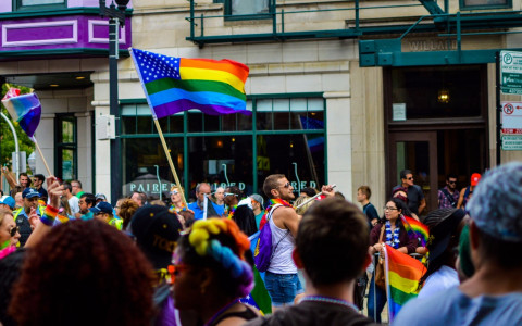 Gay Pride celebration on city street with Rainbow American flag