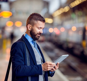 Man looking at electronic device at train station