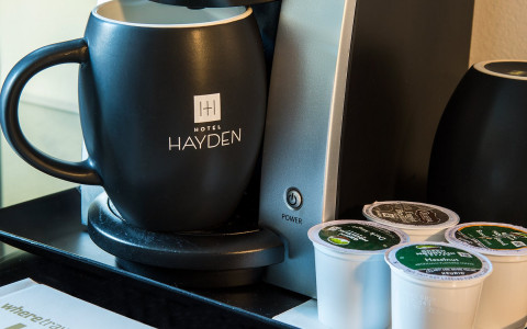 black coffee cup with Hotel Hayden printed on it