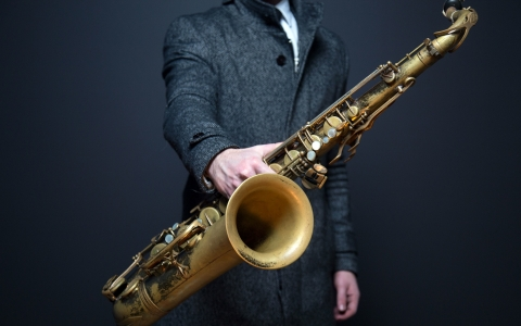 Man holds saxophone out toward viewer