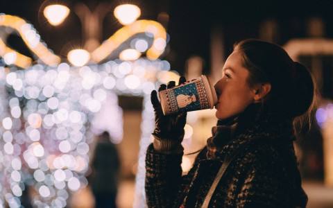 woman holding hot drink in front of Christmas lights