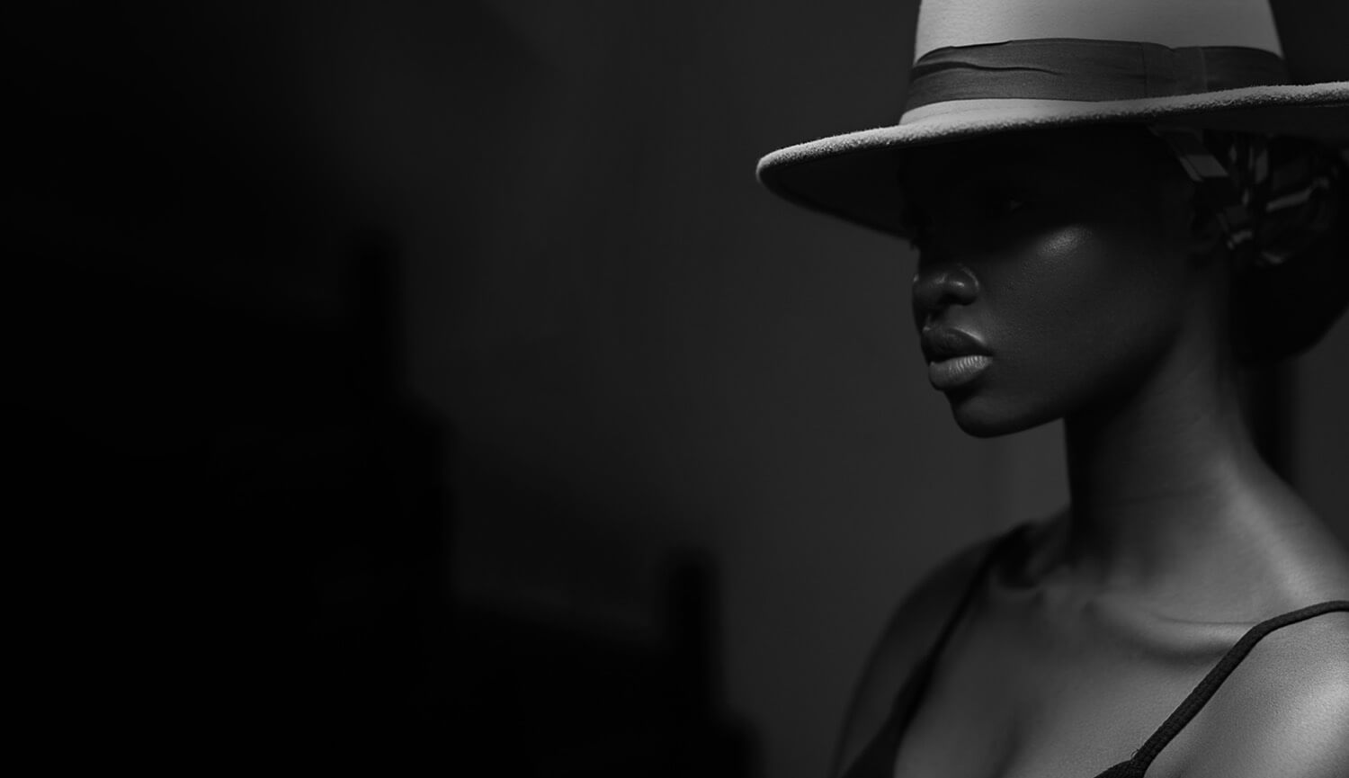 black and white image of a woman wearing a fedora hat