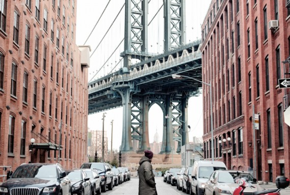 man looking at a view of a bridge in new york between two buildings