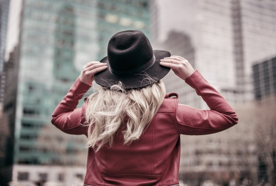 a girl holding her hat on outside in the city
