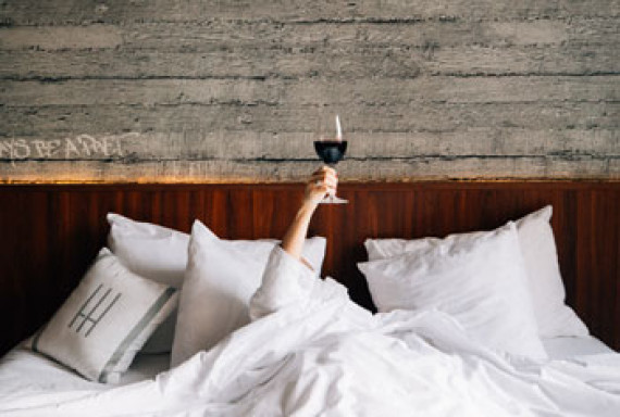 a person laying in bed with a glass of wine