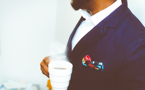 well dressed man drinking coffee