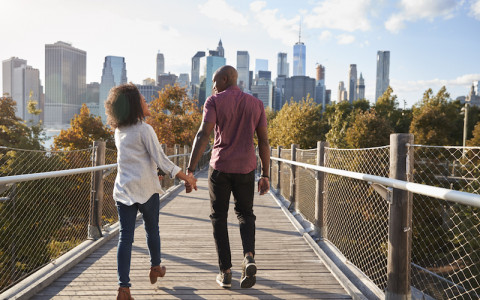 couple holding hands while walking manhattan in background