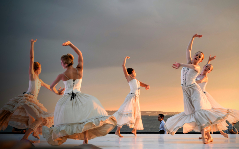Five female ballet dancers in white dresses dancing on outdoor stage