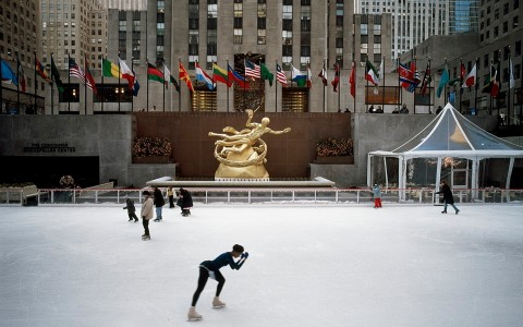 Ice skaters at Rockefeller Center in front of golden statue and national flags